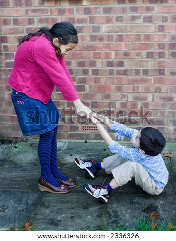 A young girl trying to pull her brother up after he trips over and fall down. - stock photo