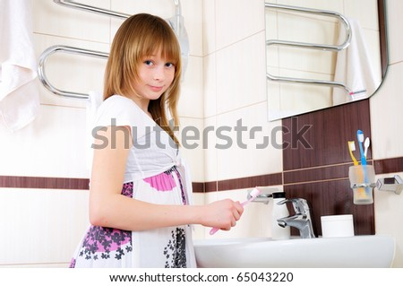 A young girl waking up early in the morning, brushing his teeth in his bathroom