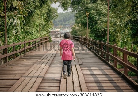 A young girl walking alone on the bridge. - stock photo