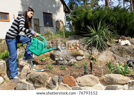 a young girl watering flowers - stock photo