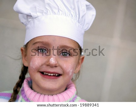 a young girl wearing a chef's hat - stock photo