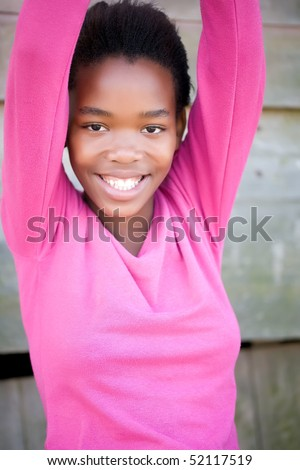 A young girl wearing a pink jersey smiling with her hands up above her head - stock photo