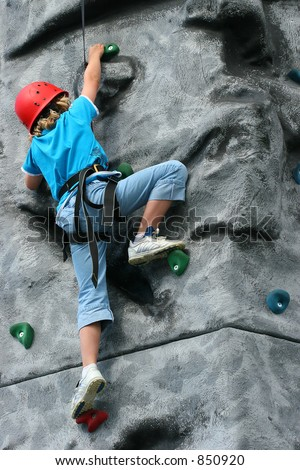 A young girl wearing a safety harness and climbing on a training rock face.