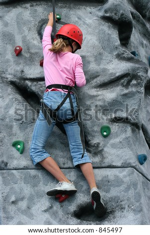 A young girl wearing a safety harness and red hard hat, climbing on a training rock face.