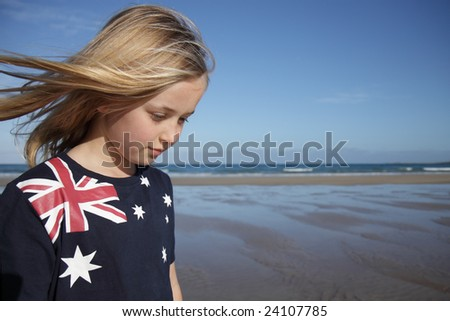 A young girl wearing an Australian flag t-shirt at the beach. - stock photo