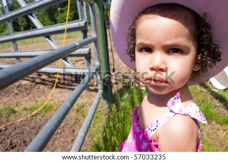 A young girl wears a pink dress, a cowboy hat, and cowboy boots on a ranch farm while petting horses and cows.