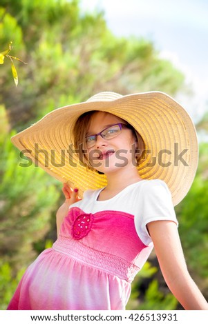 A young girl, who is missing her two front teeth, is modeling a big, floppy hat.