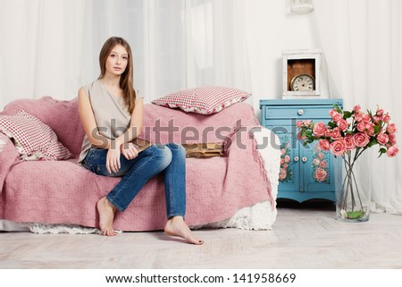 A young girl with a book on the couch - stock photo