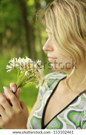 a young girl with a bouquet of flowers in nature
