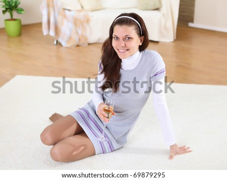 a young girl with a glass of wine or champagne at home on the carpet