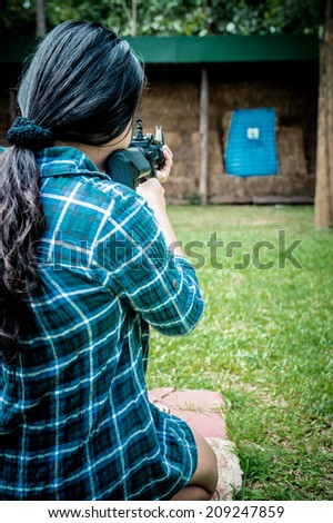 A young girl with a gun aiming at a target - stock photo