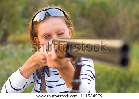 A young girl with a gun for trap shooting and shooting glasses aiming at a target - stock photo