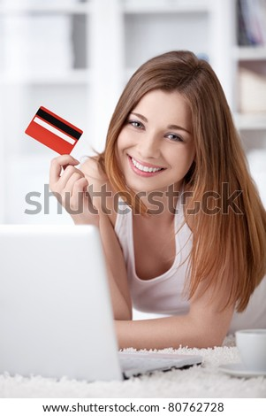 A young girl with a laptop and a credit card at home