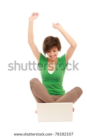 A young girl with a laptop sitting on the floor, hands up