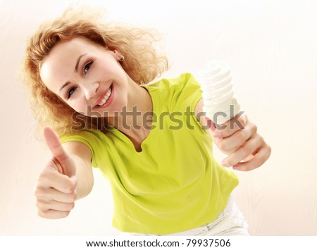 A young girl with an energy-saving bulb and showing ok, isolated on white - stock photo