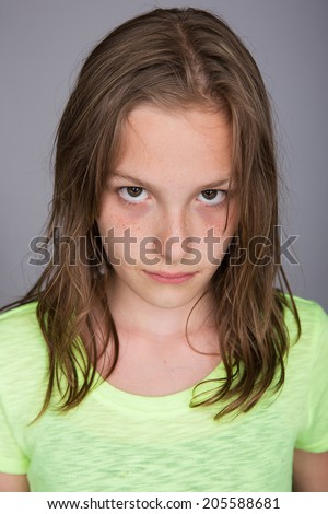 A young girl with an unhappy expression on her face - stock photo