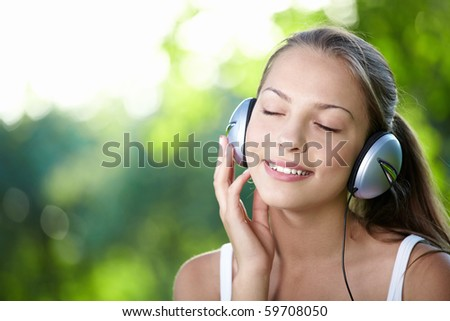 A young girl with headphones outdoors