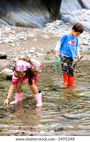 A young girl with her brother wades through shallow pool by the beach looking for sealife. - stock photo