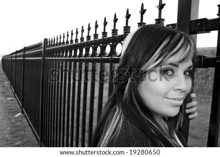 A young girl with highlighted hair posing by a fence - black and white.