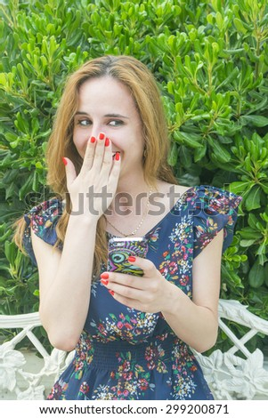 a young girl with long hair with a phone - stock photo