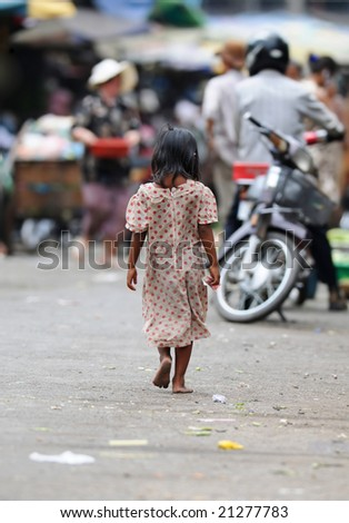 a young girl with money in her right hand on the way to a market in phnom penh - stock photo