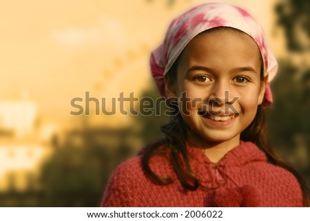 A young girl with pink bandanna showered by the glow of the evening sun - stock photo