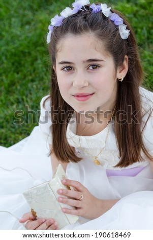 A young girl with prayer book celebrating her First Holy Communion - stock photo