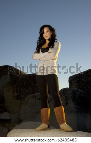 A young girl with serious attitude stands on some large boulders. Beautiful side lighting from the sunset. Lots of negative space at the top for text. - stock photo