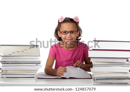 A young girl with spectacles enjoys studying large volumes of books. - stock photo
