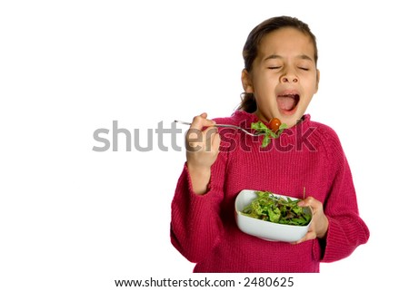 A young girl yawning showing boredom at having to eat her bowl of fresh salad, isolated on white. Concept : Healthy eating. - stock photo