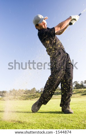 A young golfer hits the ball sending grass flying into the air (motion blur) - stock photo