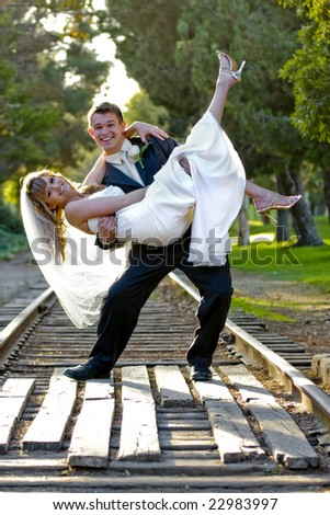 A young groom carrying his bride - stock photo