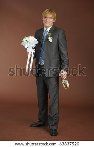A young groom with a bouquet and a bottle of sparkling wine - stock photo