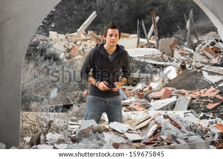 A young guy gaming amidst piles of rubble, a modern life concept - stock photo