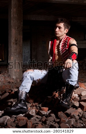 A young guy in a suit  posing on the ruins of an unusual - stock photo