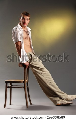 A young guy in light trousers and a white shirt posing on gray-yellow background - stock photo