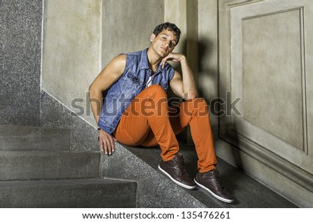 A young guy is sitting outside,  looking at you and thinking/Portrait of Young Guy - stock photo
