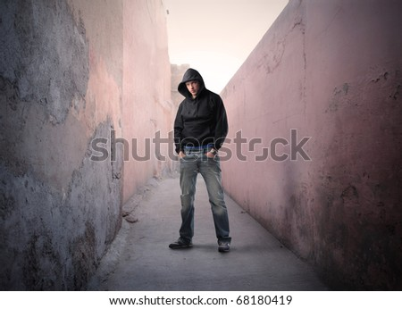 A young guy is standing in a narrow street - stock photo