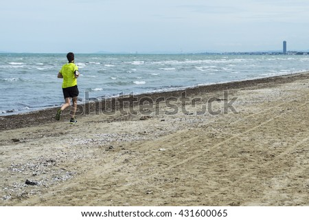 A young guy plays jogging on the beach