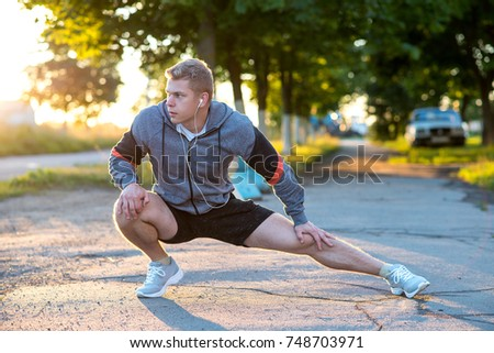 A young guy runner early morning makes gymnastics feet headphones. A warm-up joints muscles, man park listening to music, confident look. In summer, life style, motivation warming up. Outdoors city.