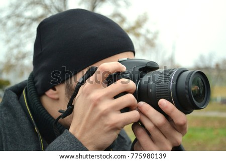 A young guy with a camera in the autumn on the street