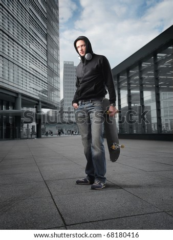 A young guy with his skateboard - stock photo