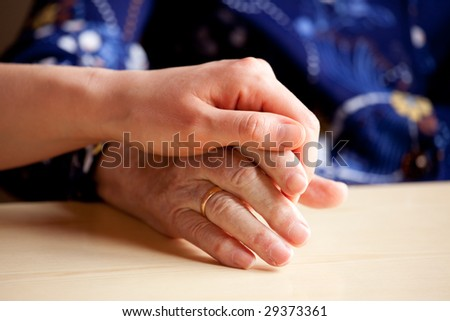 A young hand comforts and elderly hand - stock photo