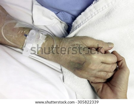 A young hand touches and holds an old wrinkled hand - stock photo
