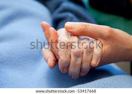 A young hand touches and holds an old wrinkled hand