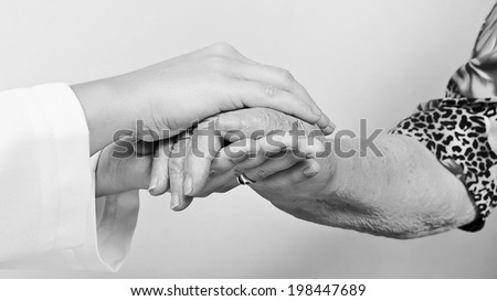A young hand touches and holds an old wrinkled hand - black and white  - stock photo