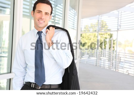 A young, handsome business man at the office building - stock photo