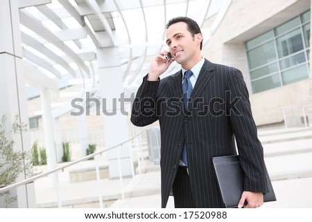 A young, handsome business man at the office building on phone - stock photo