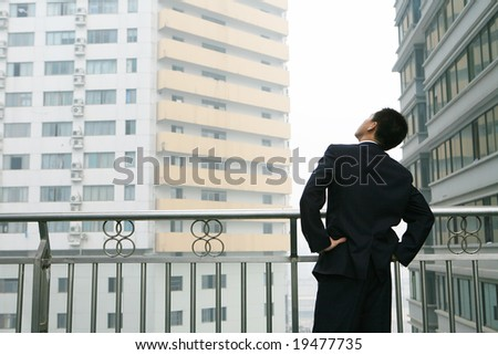 A young, handsome business man before building - stock photo