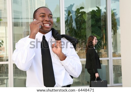 A young, handsome business man talking on his cell-phone - stock photo